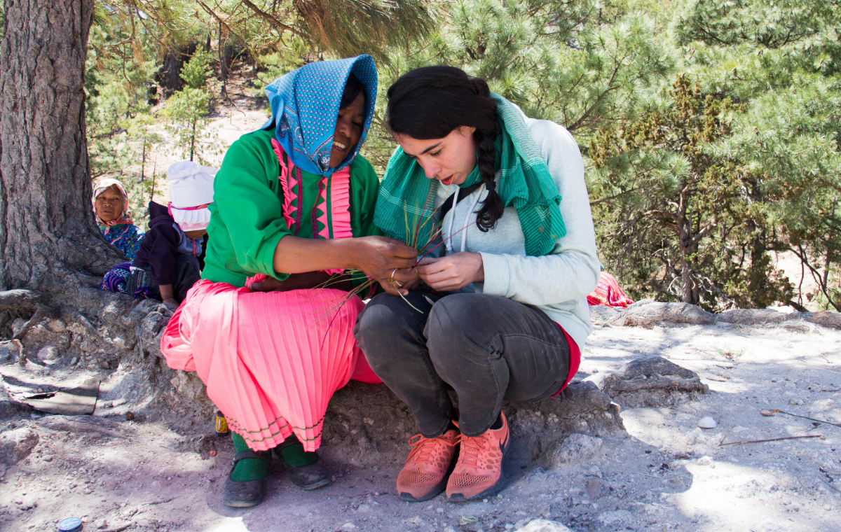 Two women sitting, Mexican woman in pink dress, green top, and blue headscark helps tourist with weaving project